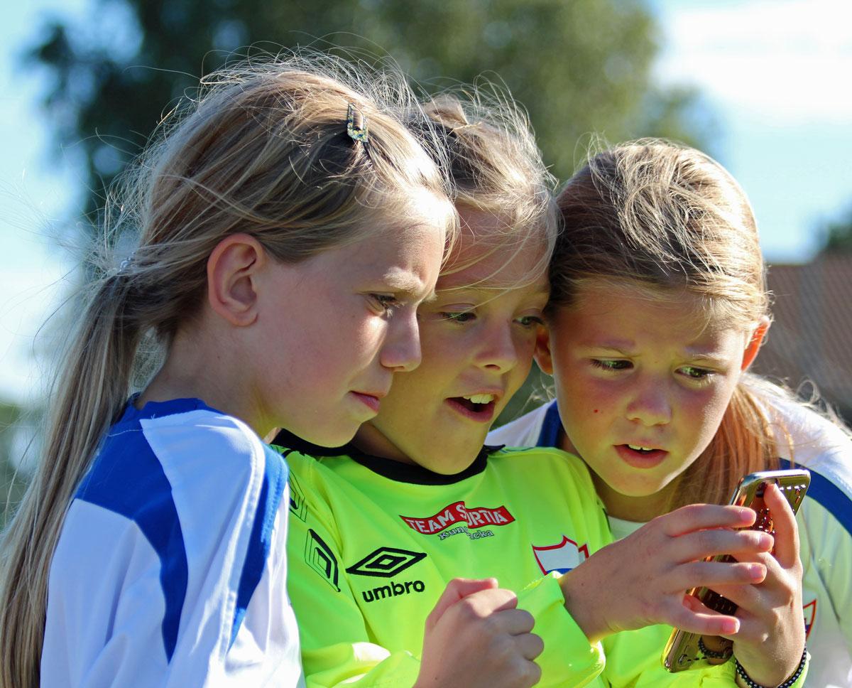 Tre tjejer står och tittar på en mobil. De har fotbollskläder på sig.