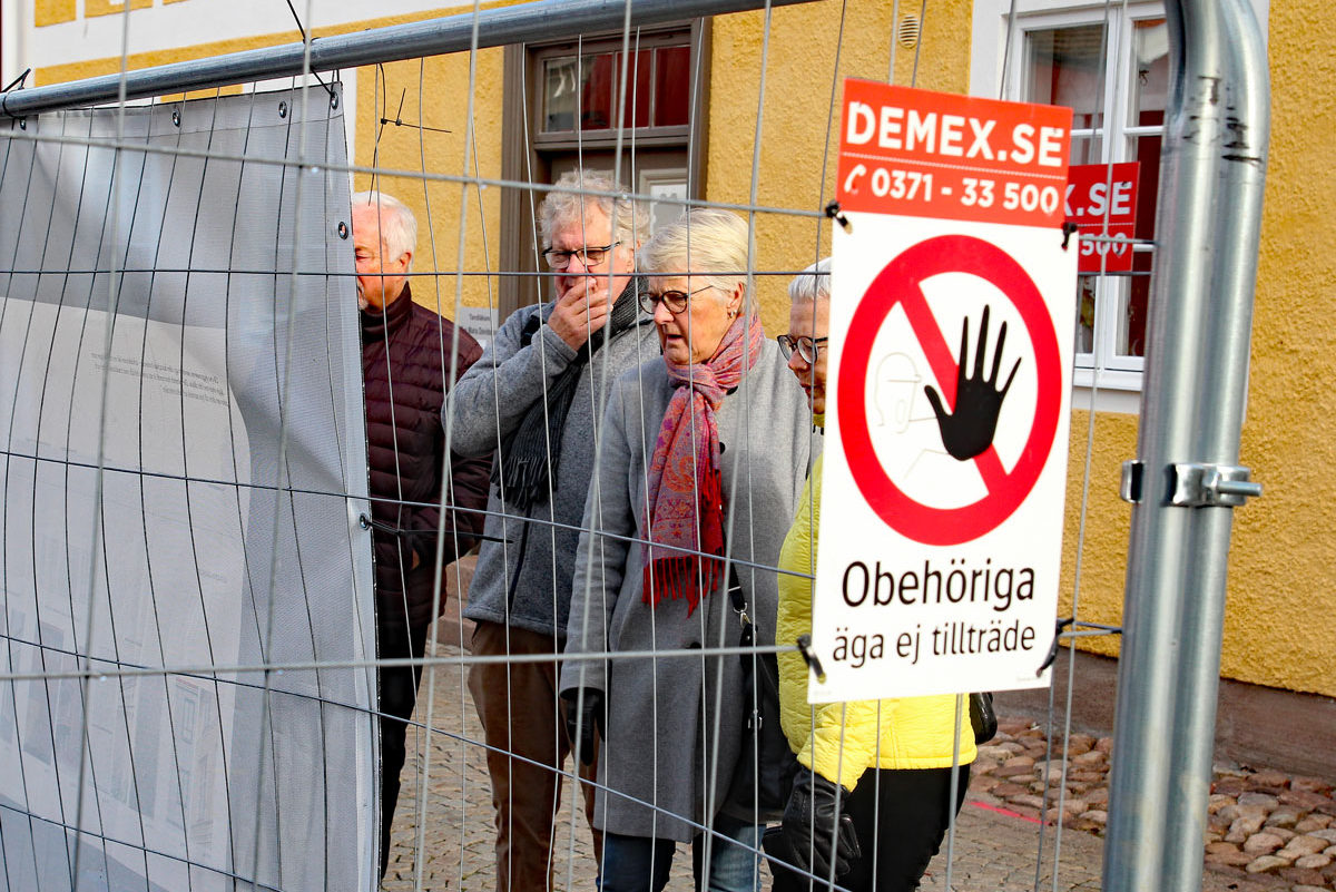 """Flera gamla personer står utanför ett staket och tittar förfärat in genom staketet. På staketet sitter det en skylt där det står """"Obehöriga äga ej tillträde""""."""