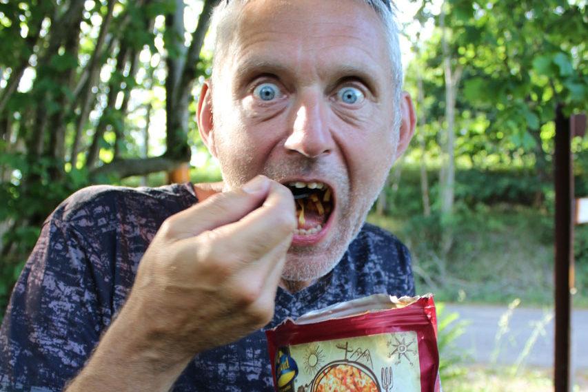 En person tar en stor sked med mat samtidigt som den tittar rakt in kameran med lite galen blick.