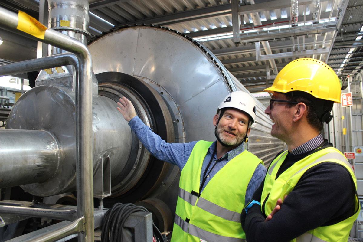 Två personer i reflexvästar och hjälmar står vid en stor maskin. Den ena pekar på maskinen och båda skrattar.