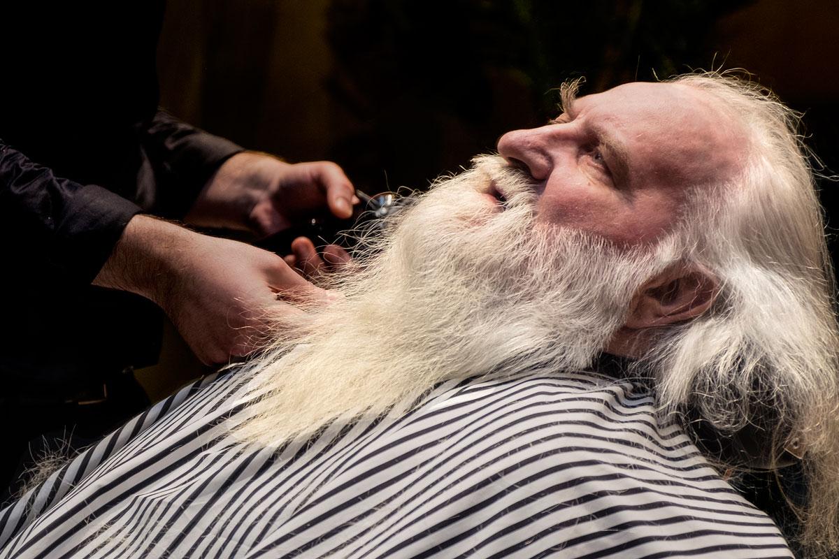 En man ligger ner i en frisörstol. Han har ett stort skägg och mustasch. En person håller fram en rakapparat mot skägget.