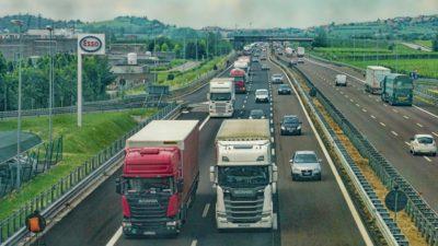 Flera stora lastbilar kör på en trafikerad väg.