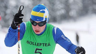 Zebastian Modin kämpar på sina skidor. Han har ett par svarta, mörkläggande glasögon för att alla ska tävla på samma villkor.
