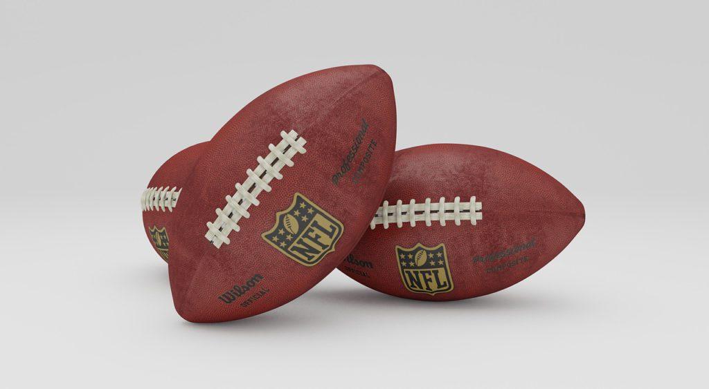 Två amerikanska fotbollar ligger bredvid varandra. De är ovala, men spetsiga.