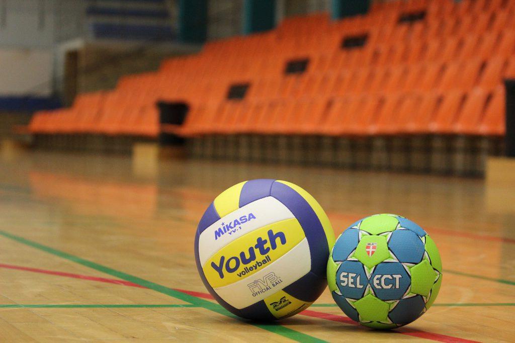 Två handbollar ligger på ett golv i en idrottshall.