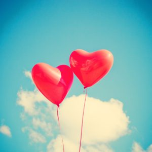 Två ballonger formade som hjärtan svävar i luften framför ett moln.