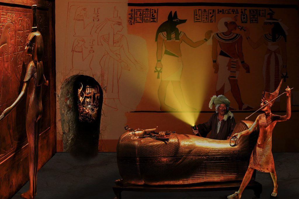 En egyptisk gravkammare med en kista som är formad som en person. Runt kistan står det statyer och bakom kistan står det en person med ficklampa och ser glad ut.