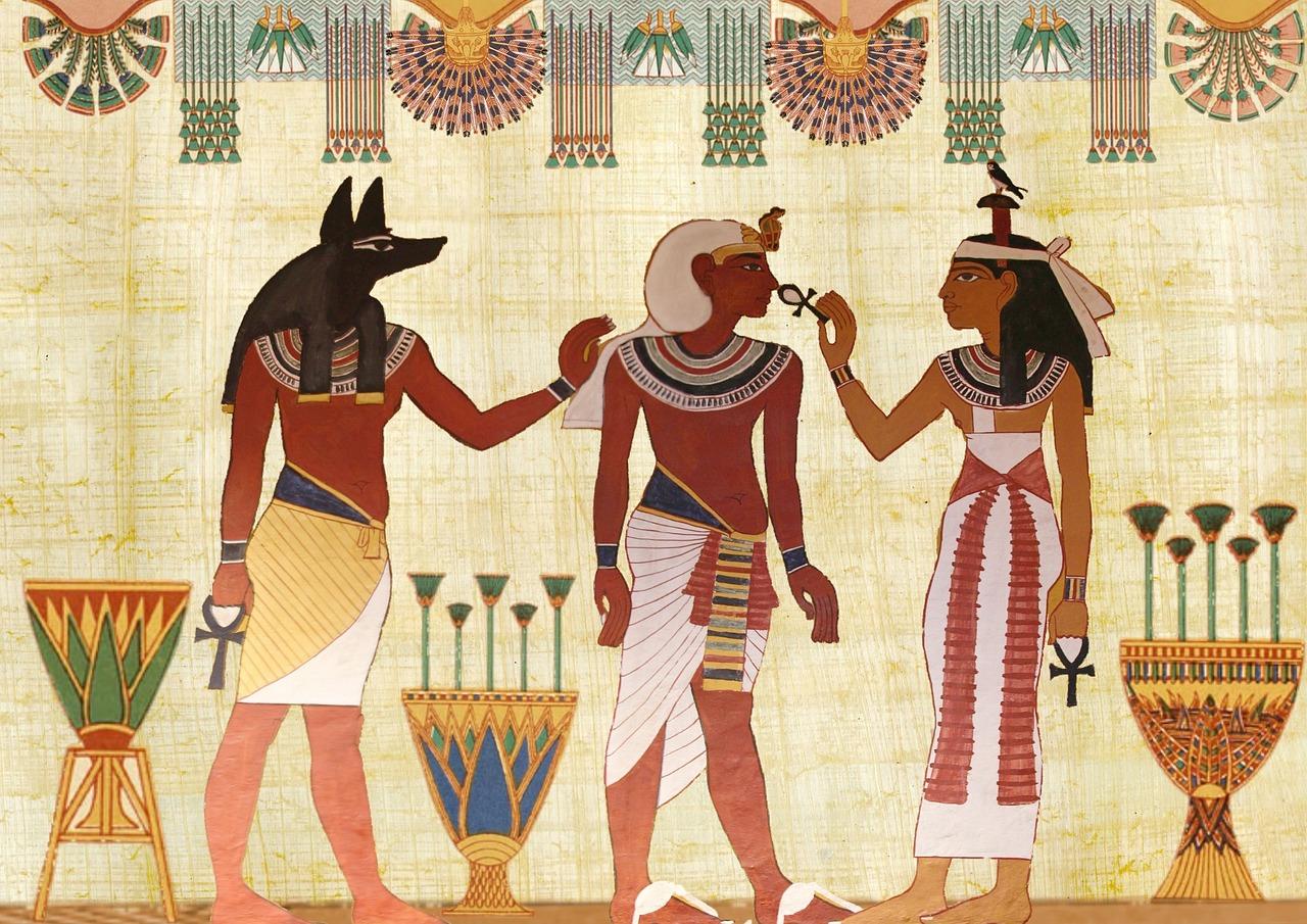 En bild från gamla Egypten målad på en vägg. Den förställertre personen. En kung i mitten och två personer bredvid honom, en som håller upp en symbol mot hans ansikte och en med varghuvud som håller på hans axel.