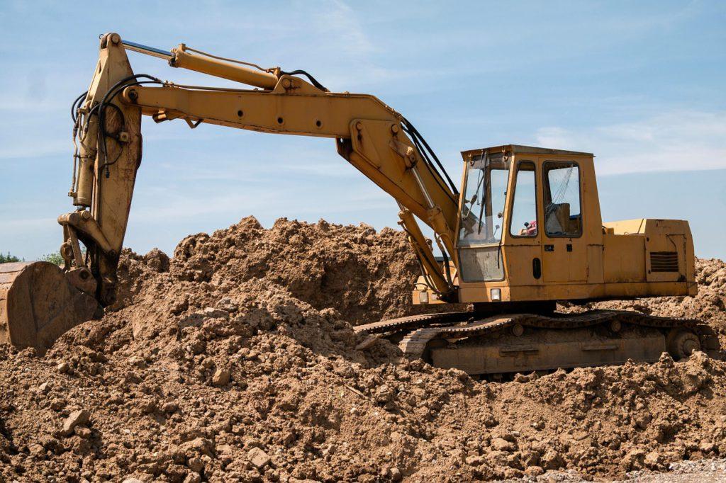 En grävskopa står i ett sandtag och gräver.