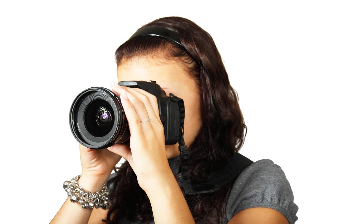 En person står och tittar genom en stor kamera. Personen har långt hår, diadem och ett stort glittrigt armband.