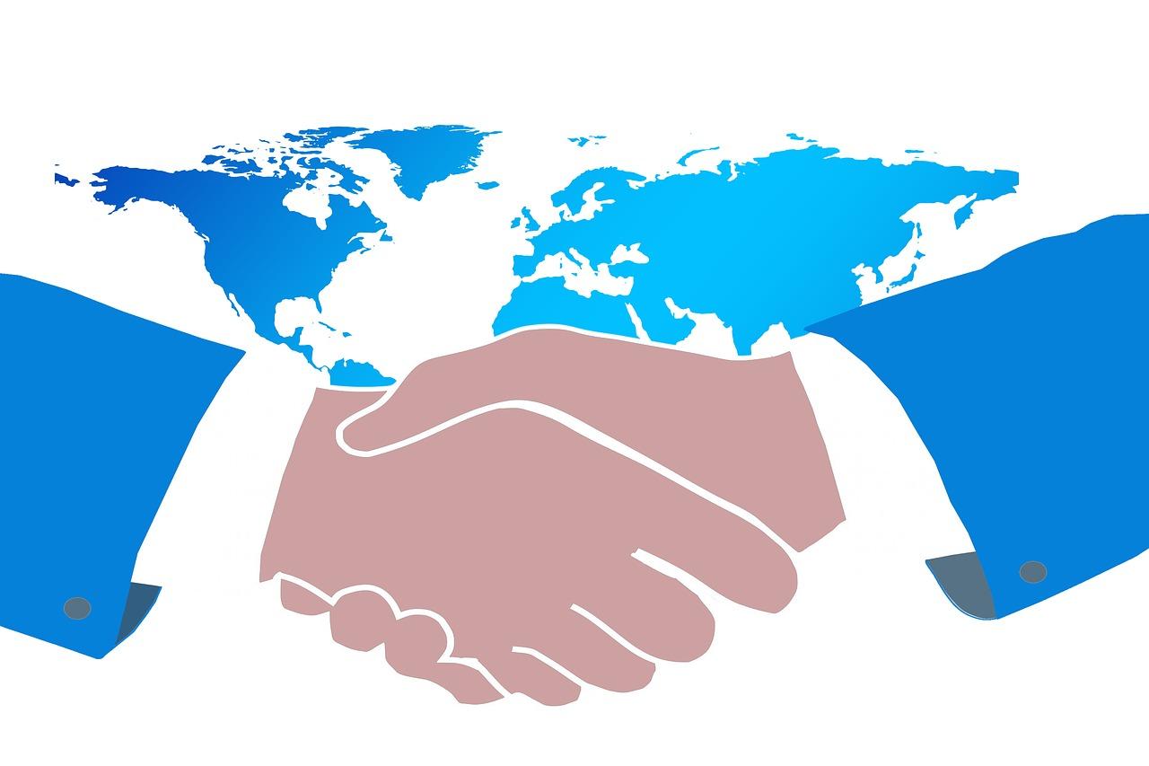 Två händer som skakar hand framför en världskarta.