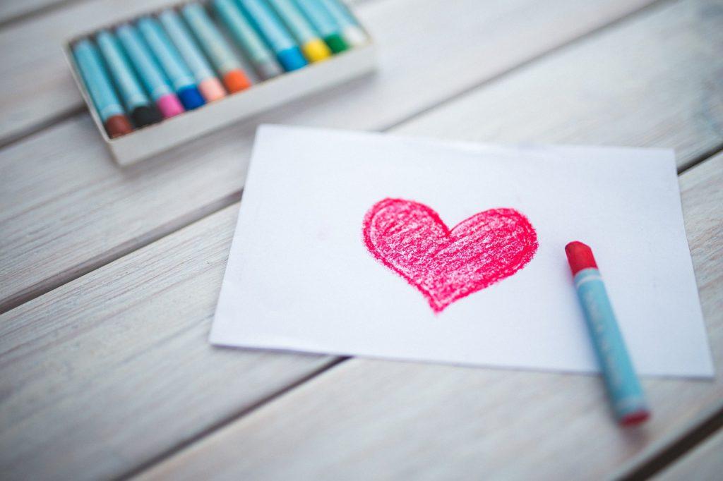 Ett hjärta ritat på ett papper. Bredvid ligger det färgkritor.