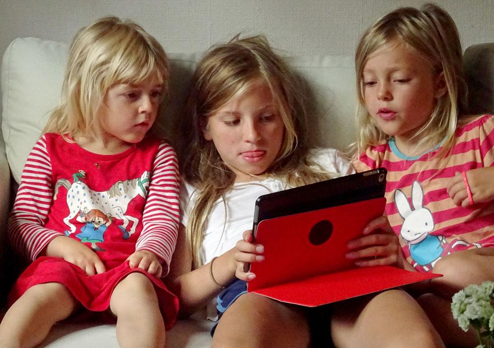 Tre barn sitter i en soffa. Den i mitten håller i en platta som alla tittar på.