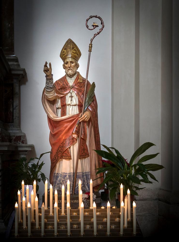 En staty av Valentinus. Han har en lång dräkt, en mantel, en hatt som är trekantig och han håller i en lång stav med krok på. Runt statyn är det massa ljus tända.