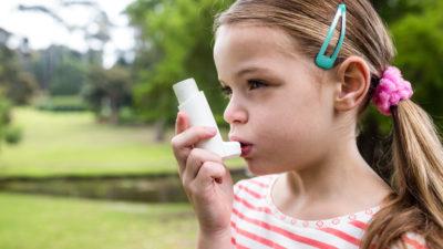 Ett barn står utomhus. Det har långt hår med tofsar och spännen i. Barnet håller en avlång plastgrej framför munnen