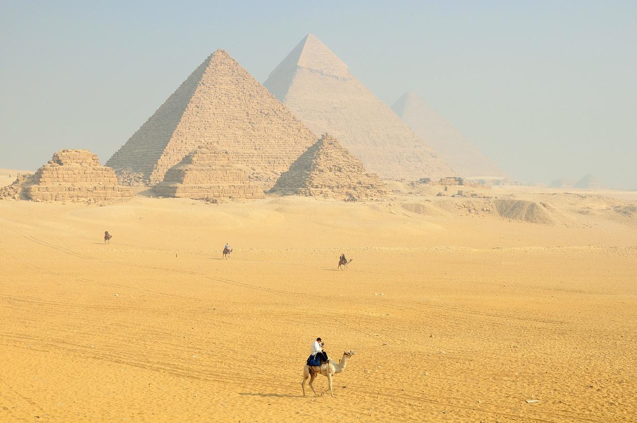 Flera stora pyramider står i en öken. Solen lyser starkt.
