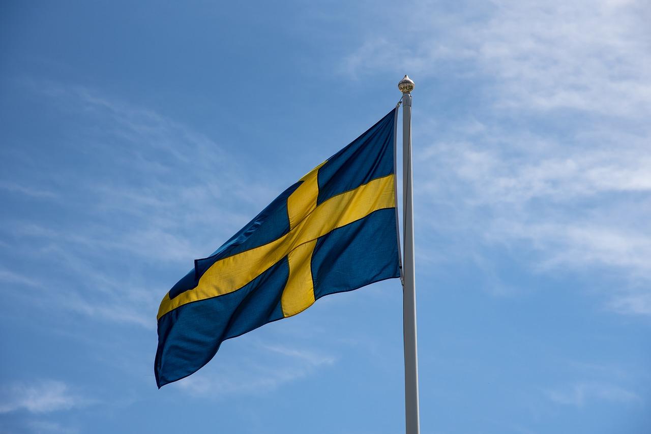 En svensk flagga vajar i vinden på en flaggstång.