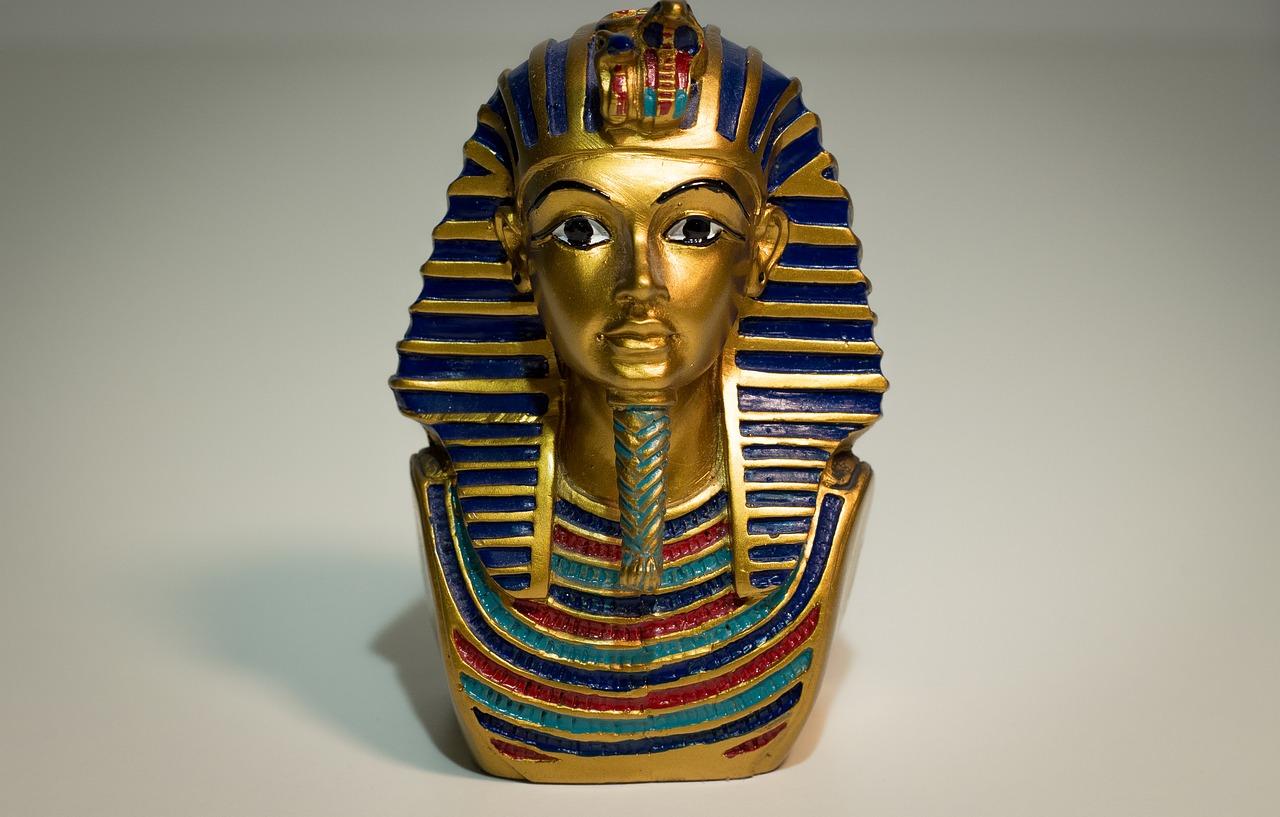 En guldig staty av Tutankhamun. Han har skägg på hakan som är flätat och över hans hår ligger som en duk som också är randig av guld.