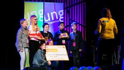 Sex elever står på scen. Några håller i en stor värdecheck och några håller i varsin ask med choklad.