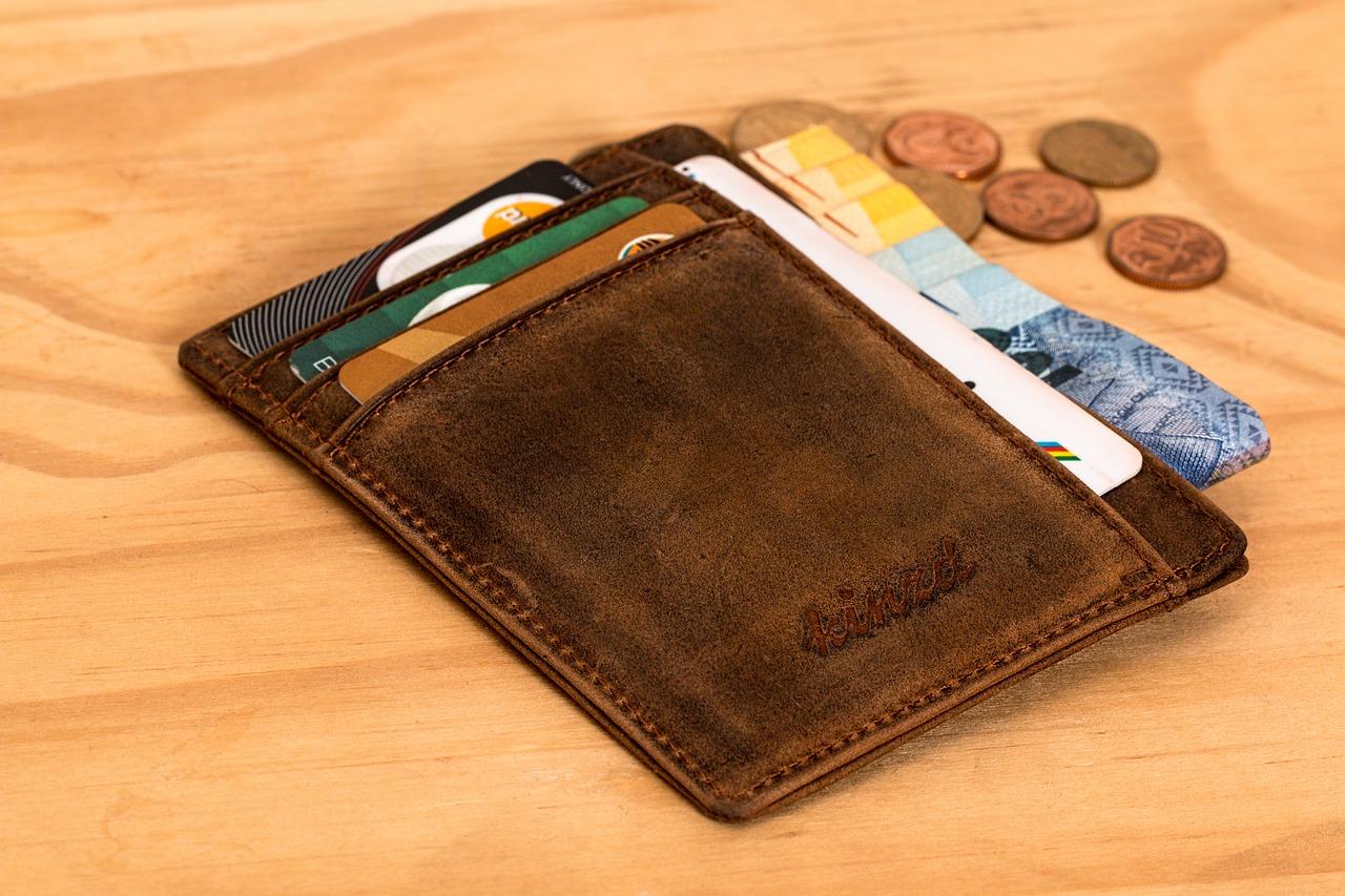 En plånbok ligger på ett bord. Det sticker upp kort ur plånboken och det ligger mynt bredvid på bordet.