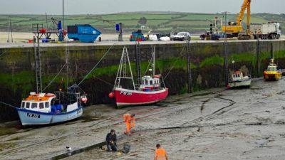 En hamn utan vatten. Längs med hamnkanten ligger det flera båtar på bottnen. På bottnet står flera personer i reflexkläder och gräver i gyttjan. Personerna ser lite konstiga ut i bilden, som att de är inklippta.