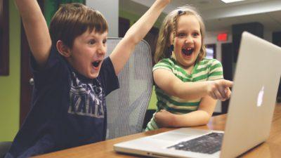 Två barn sitter framför en dator och jublar. Genom ansiktsuttrycken visar de att de är otroligt glada, men kanske också lite förvånade.