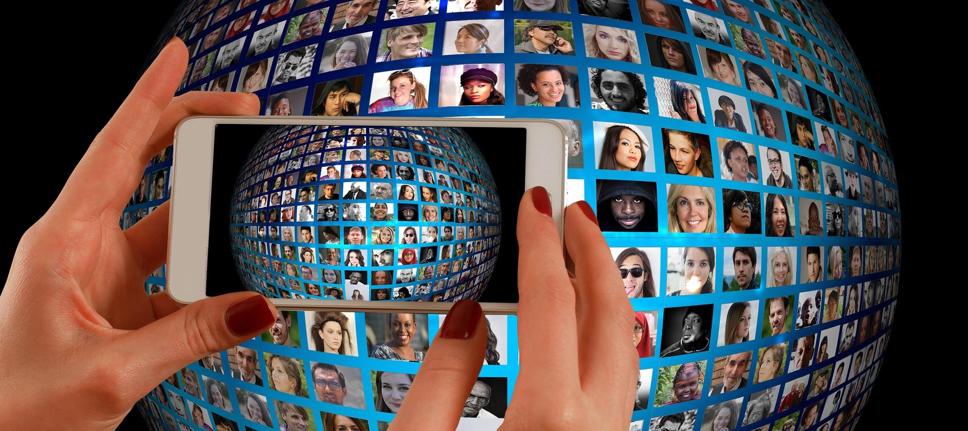 Massa bilder på ansikten på ett runt klot. Framför klotet håller någon upp en mobil och fotar bilderna.