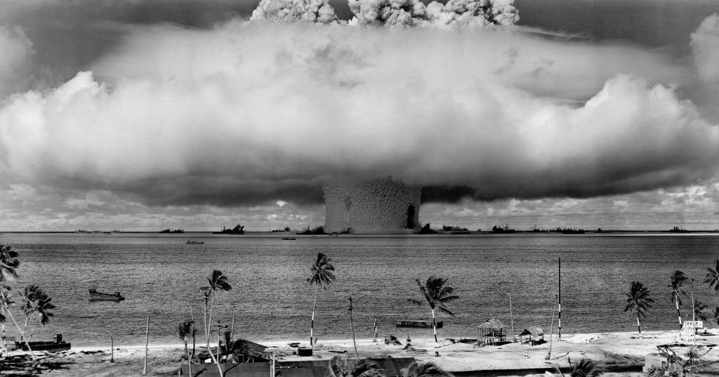En atombomb sprängs i fjärran. Ett stort svampliknande moln stiger mot himlen.