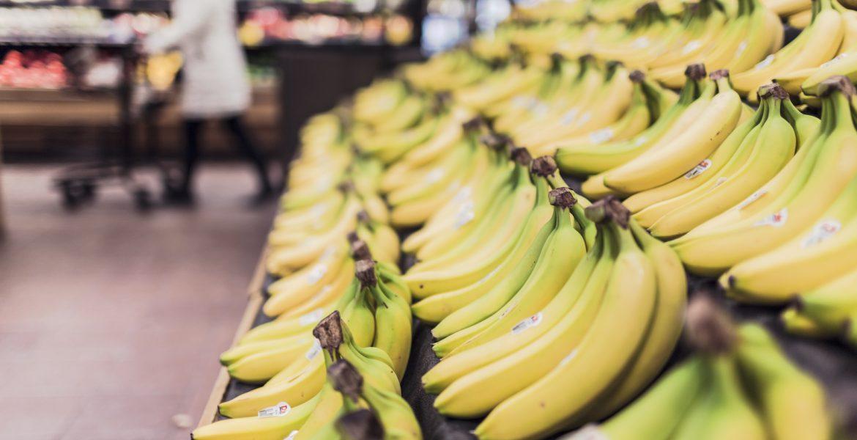 Bananer ligger uppradade snyggt på en hylla i en butik.
