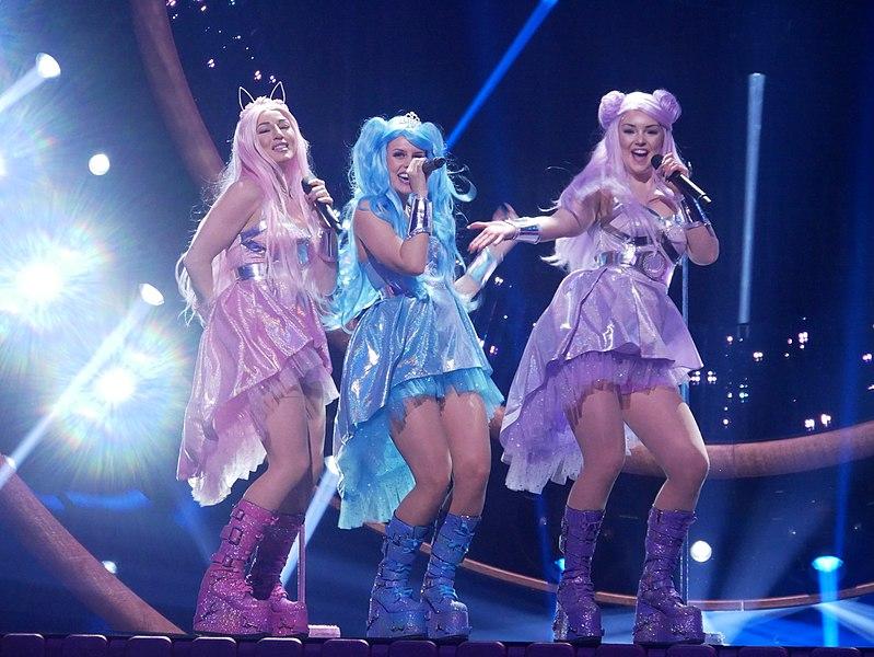 Dolly Style i färgglada kläder och peruker på scenen på Melodifestivalen.