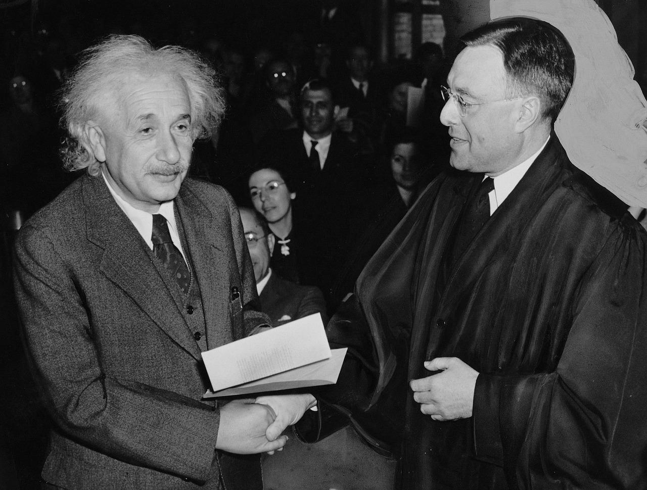 Einstein står och skakar hand med en person i lång svart kappa. Einsten har stort vitt yvigt hår och ser lite finulrig ut.