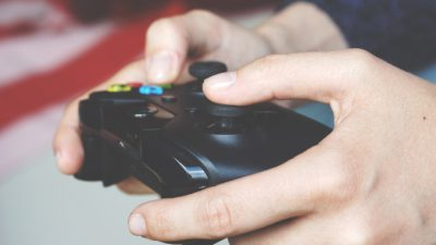 Bild på två händer som håller i en spelkonsol för TV-spel.