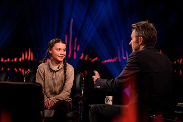 Greta Thunberg ler där hon sitter i en fåtölj i en TV-studio och blir intervjuad av den norska programledaren Fredrik Skavlan.