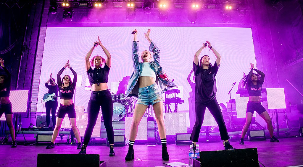 Zara Larsson står och sjunger på scen. Hon har armarna högt i luften, precis som hennes dansare bakom henne.
