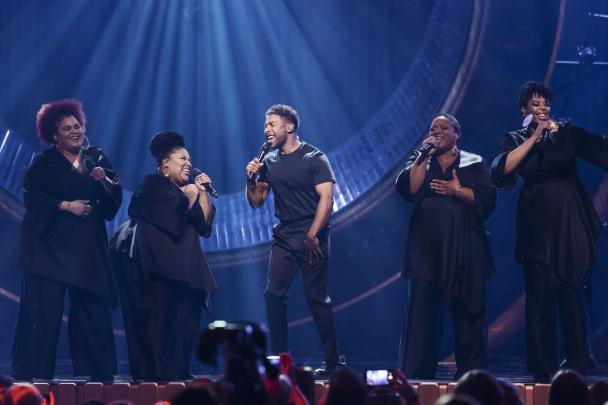 John Lundvik och hans gospelkör tar i och sjunger på scenen under Melodifestivalen.
