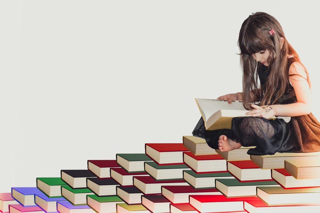 Ett barn sitter på en hög med böcker och läser.
