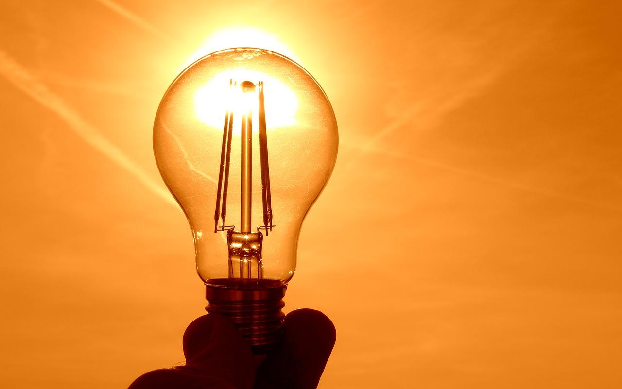 En hand håller i en glödlampa som soler lyser genom.