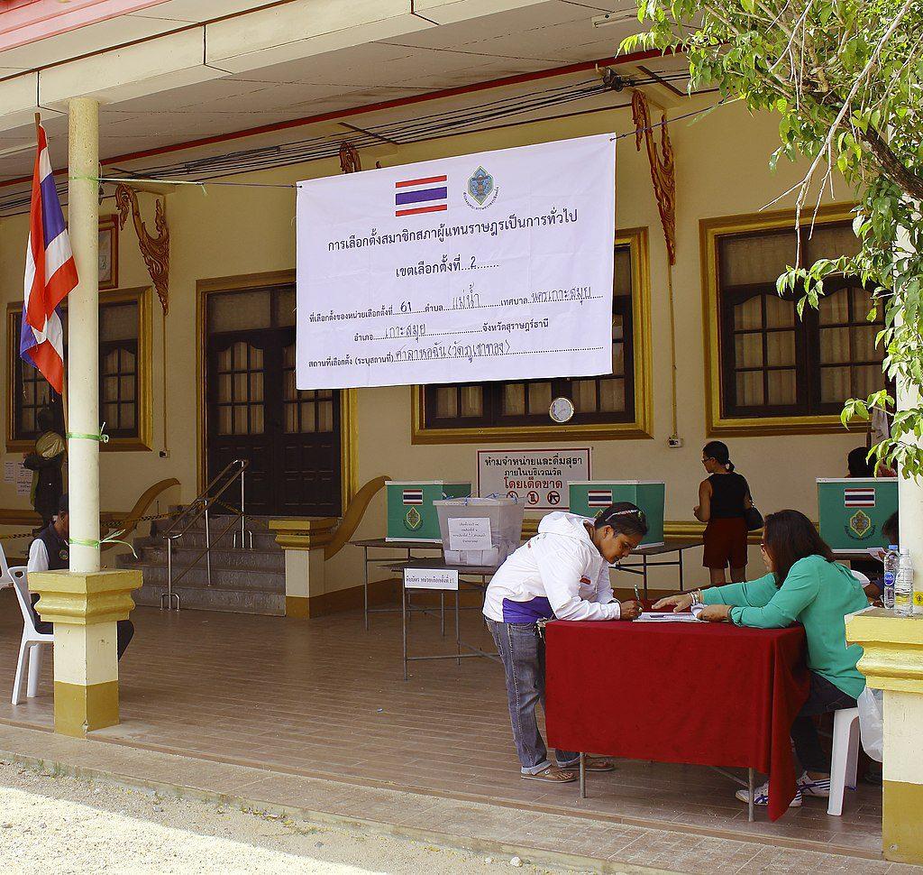 Bilden visar en vallokal. En person böjer sig fram över ett bord för att fylla i sina uppgifter för att få rösta.