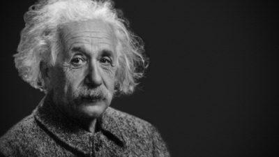 Albert Einstein sitter och tittar mot kameran. Han har stort rufsigt vitt hår, en stor mustasch och ganska många rynkor i pannan. Han ser snäll men lite trött ut.