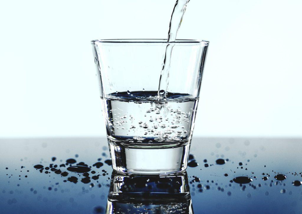 Vatten hälls i ett vattenglas.