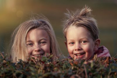 Två glada barn som kikar fram bakom en buske.