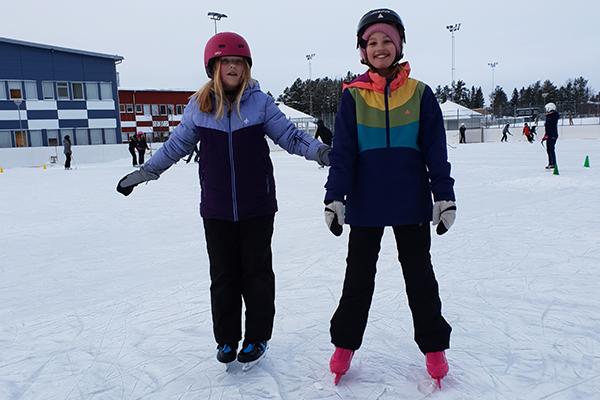 Elin och Alicia åker skridskor.
