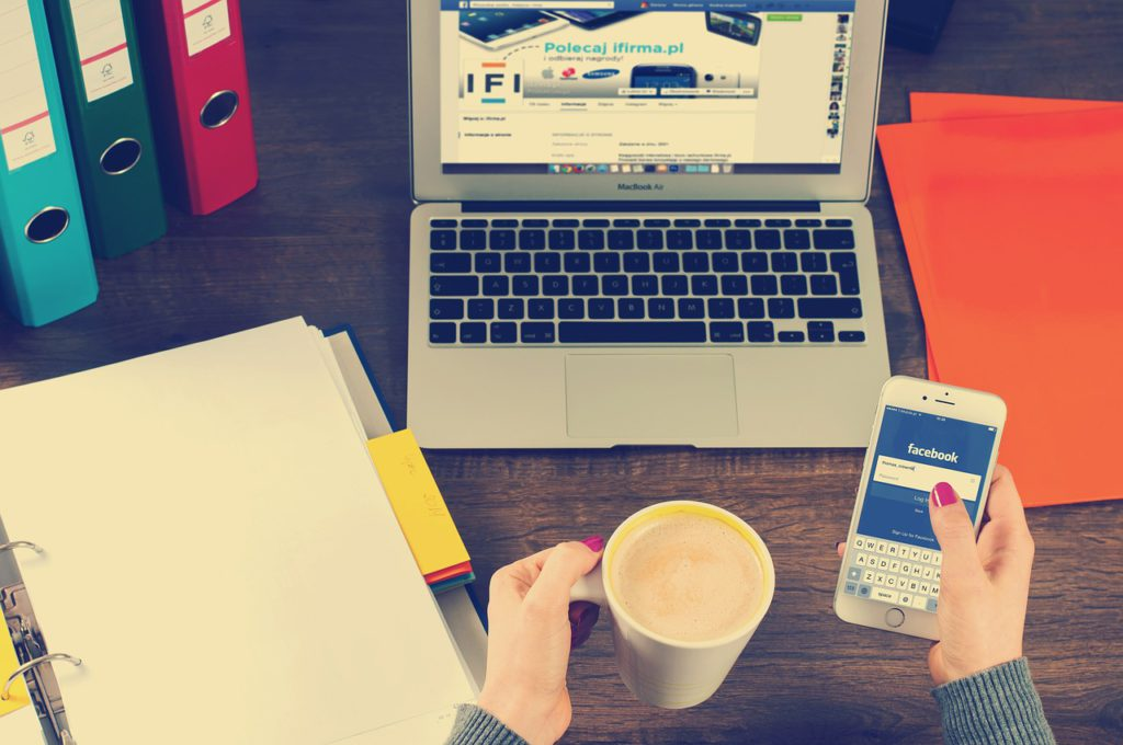 Bild på ett skrivbord där det står en laptop, en pärm, en mobiltelefon och en hand som håller i en kaffe.