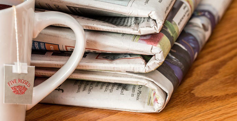 En kopp te står redo för att drickas och flera papperstidningar ligger bredvid.