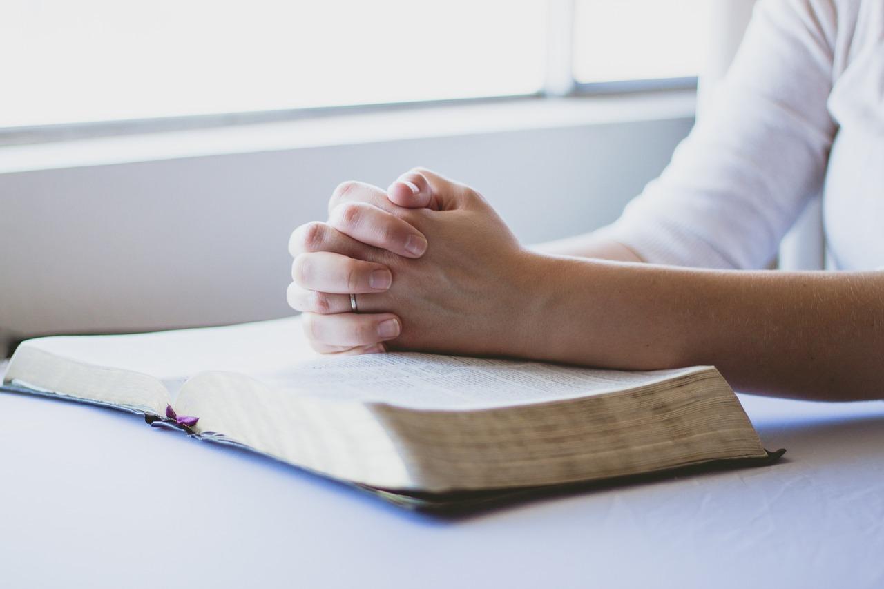 Två knäppta händer ovanpå en öppen bok.