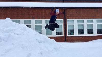 Foto på elev som hoppar i snöhög.