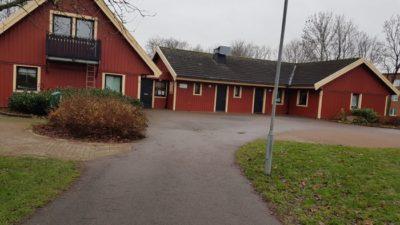 Röda hus runt en grusplan.