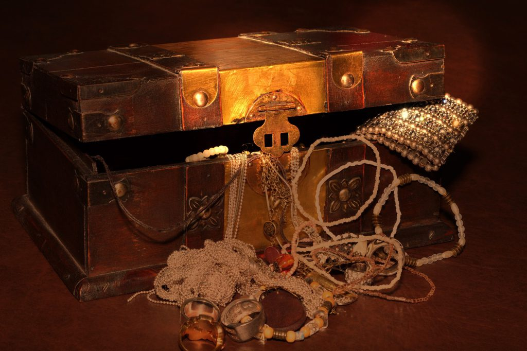 En skattkista som är gjord av trä. Ur kistan hänger det ut halsband, armband och ringar gjorda av silverpärlor, träpärlor och lite silver.