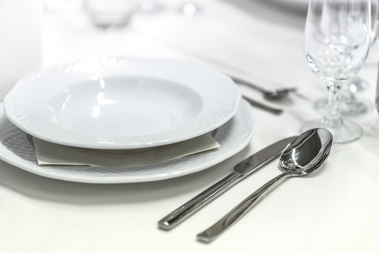 Ett dukat bord med tomma tallrikar, oanvända bestick och tomma kristallglas.