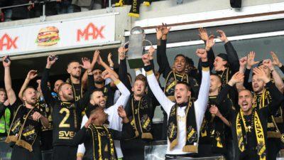 Bild på AIK:s lag som tillsammans höjer bucklan.